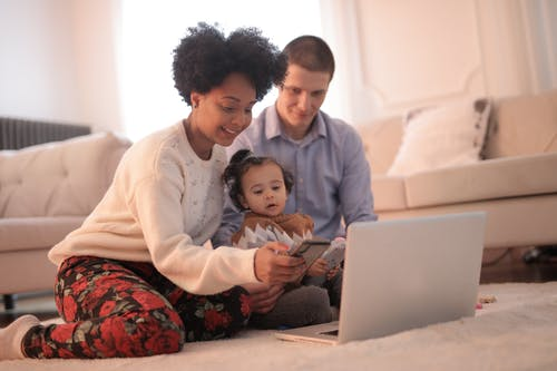 A couple with a toddler looking at a computer