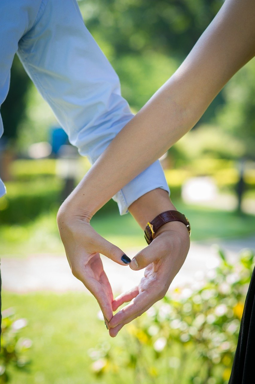 Couple holding hands in shape of heart